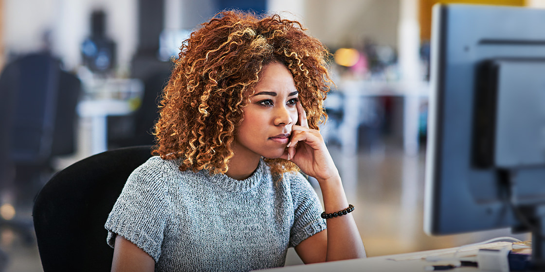 A woman ponders email processing and email processing systems.